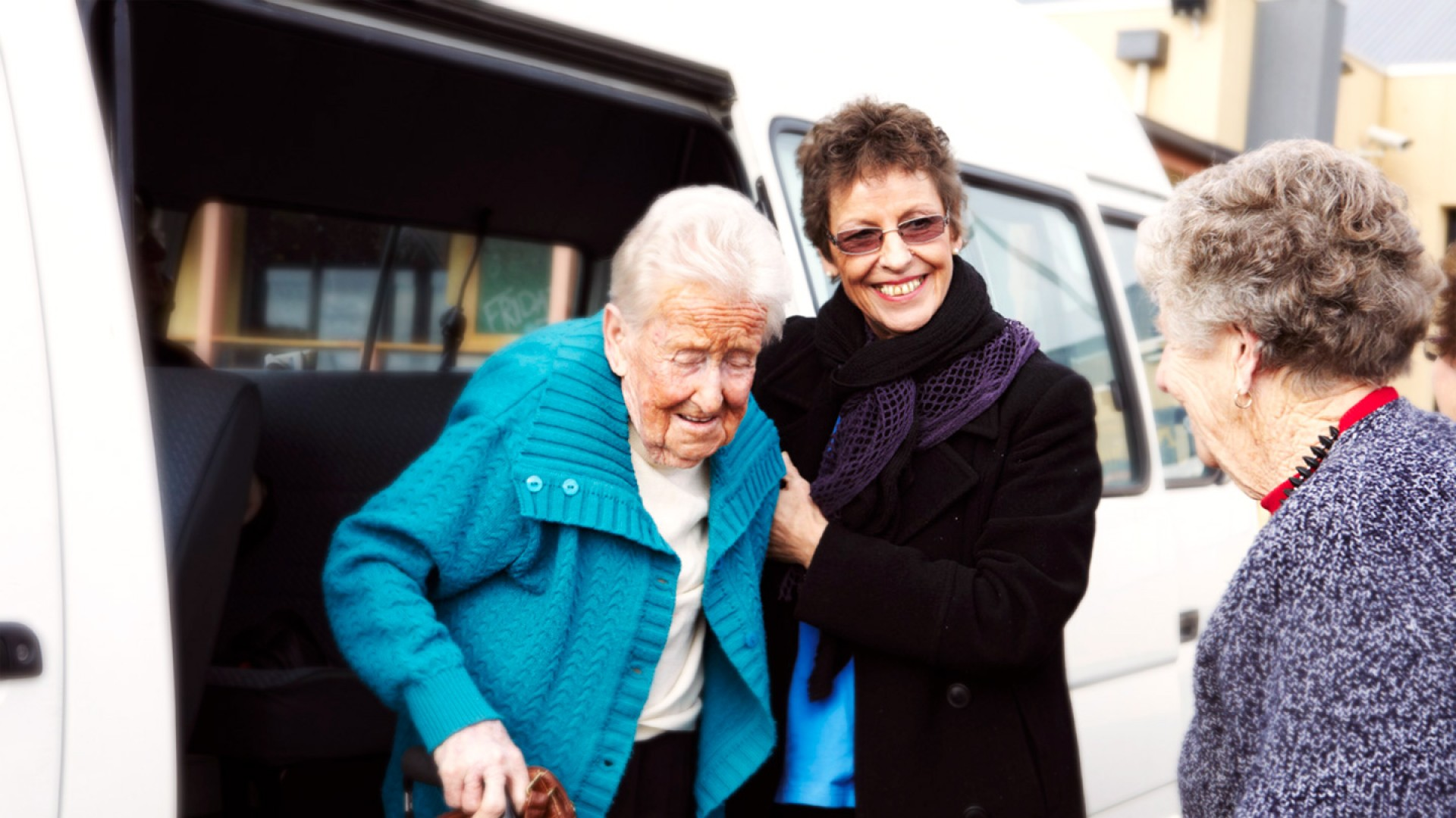 carer with elderly woman getting out of van